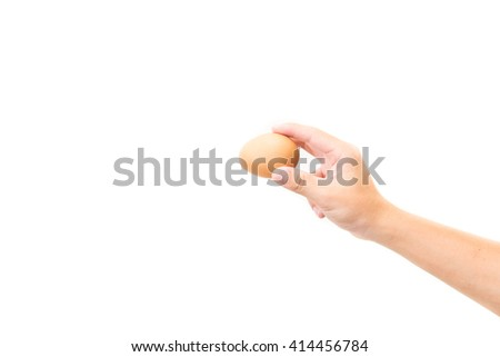 Hand holds a brown egg on a white background #414456784