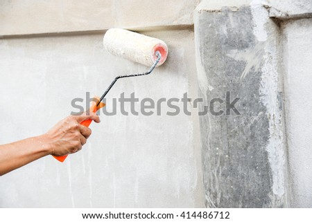 female hand painting wall with paint roller #414486712