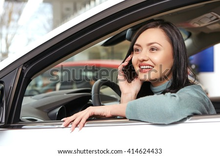 Greatest news. Low angle closeup shot of a beautiful happy brunette woman talking on the phone sitting in a brand new car at the car salon #414624433