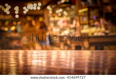 Real wood table with light reflection on scene at restaurant, pub or bar at night. Blurred background for product display or montage your products with several concept idea and any occasion. Royalty-Free Stock Photo #414699727