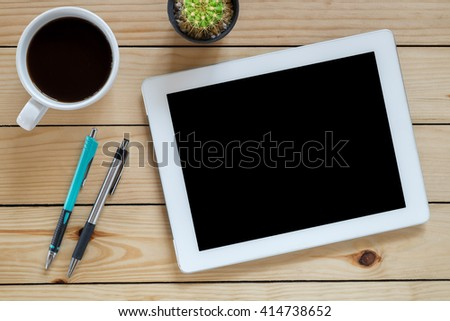 Office stuff with blank screen tablet,pen,pencil and coffee cup on rustic wood table.Top view.Office stuff concept.Flat lay images.Office supplies and gadgets on desk table.