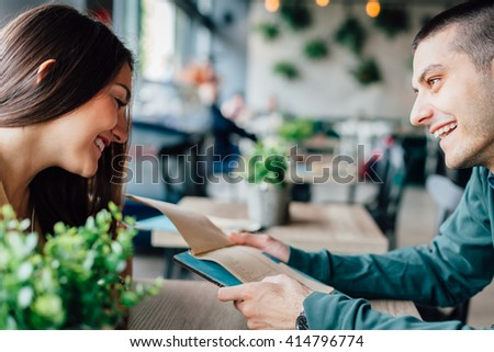 Happy young couple in a cafe looking at menu #414796774