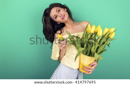 Smiling girl with yellow tulips. green background #414797695