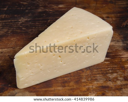 Piece of cheese on the dark brown old wooden cutting board  #414839986