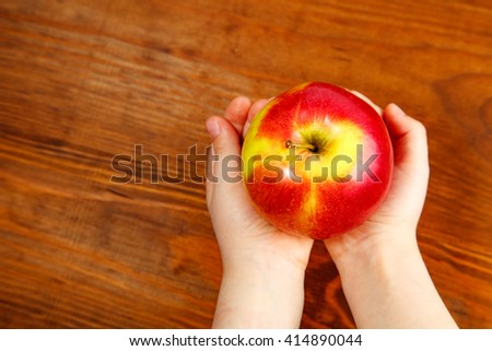 Child holding a red apple on wooden background. Top view #414890044