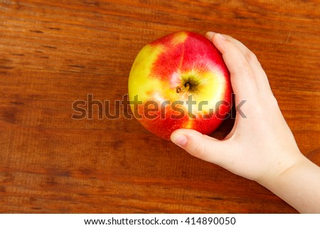Clouse up child's hands with big red apple. Top view #414890050