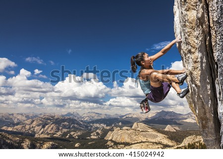 Female climber dangles from the edge of a challenging cliff. #415024942