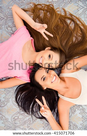 Beautiful girls lying on bed and gesturing with two fingers #415071706