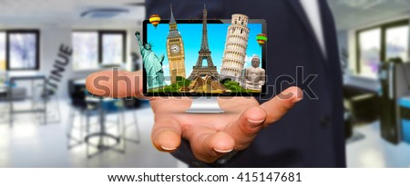Young man holding computer full of famous monuments of the world in his hands #415147681