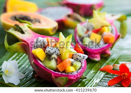 Exotic fruit salad served in half a dragon fruit Royalty-Free Stock Photo #415239670