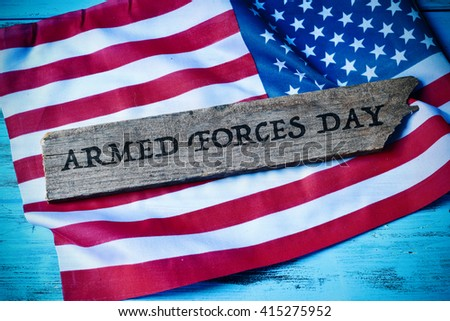 the text armed forces day written in a piece of wood and a flag of the United States, on a blue rustic wooden background, with a slight vignette added #415275952