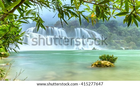 Lonely island the Ban Gioc waterfall with velvety water flow down river side fluted foliage foreground of misty air of the morning calm as a picture wearing on earth