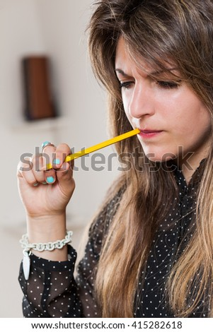 biting pencil woman is a student or a business woman #415282618