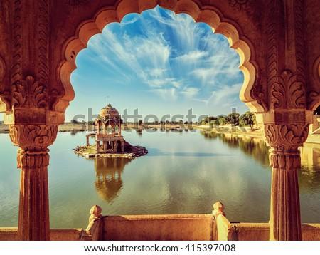 Vintage retro effect filtered hipster style image of Indian landmark Gadi Sagar - artificial lake view through arch. Jaisalmer, Rajasthan, India Royalty-Free Stock Photo #415397008
