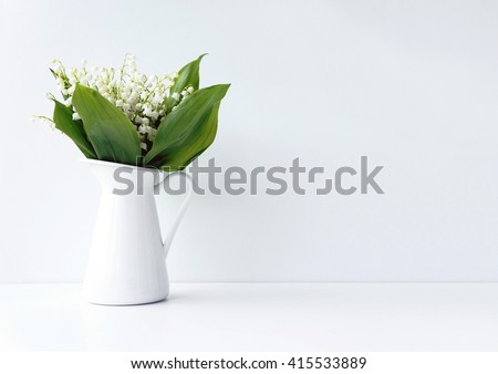 White flowers in a jar on the white background. Styled photo. Lilly-of-the-valley photo. #415533889