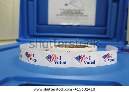 "A spool of Red white and blue ""I voted"" stickers with American flag are on a blue voting booth platform."