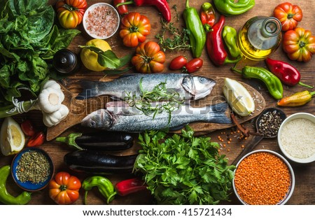Raw uncooked seabass fish with vegetables, grains, herbs and spices on chopping board over rustic wooden background, top view Royalty-Free Stock Photo #415721434