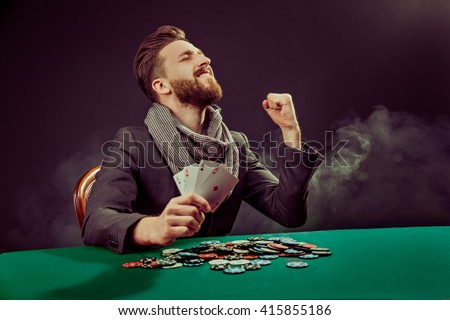 Successful poker player enjoying his win at poker table with chips and cards #415855186