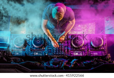 Charismatic disc jockey at the turntable. DJ plays on the best, famous CD players at nightclub during party. EDM, party concept. Royalty-Free Stock Photo #415922566