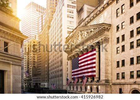 Famous Wall street and the building in New York, New York Stock Exchange with patriot flag Royalty-Free Stock Photo #415926982
