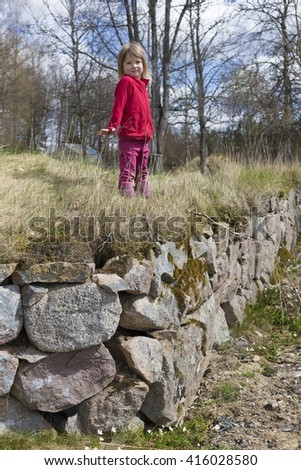 small cute scandinavian girl in red clothing playing in the swedish countryside and staying on rocks #416028580