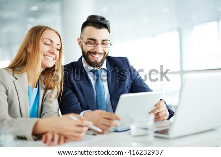 Happy businessman with his female colleague using touchpad #416232937