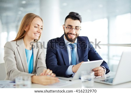 Man and woman discussing business on touchpad #416232970