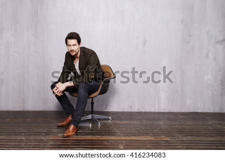 Handsome guy in chair looking at camera Royalty-Free Stock Photo #416234083