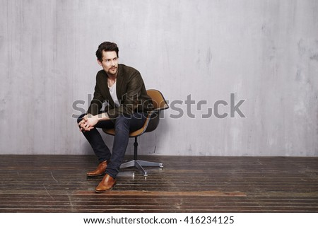 handsome young man in chair, looking away Royalty-Free Stock Photo #416234125