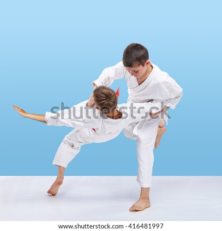 Boys in judogi are training throws on a light background #416481997