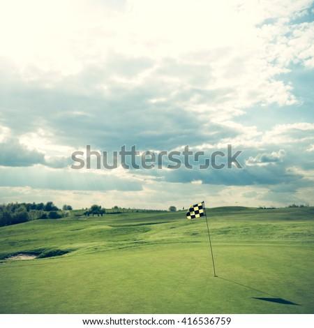 Golf course - flag against dramatic sky #416536759