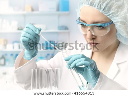 Young female tech or scientist loads liquid sample into test tube with plastic pipette. Shallow DOF, focus on the hand with the tube. #416554813