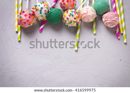 Party background. Colorful  bright cake pops and paper straws on  grey textured  background. Selective focus. Place for text.