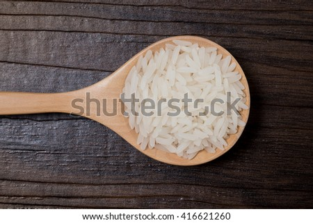 Top view closeup Rice on wooden spoon in brown wood background. Side light and 45 degree view angle and lens vignette Rice from Thailand  #416621260