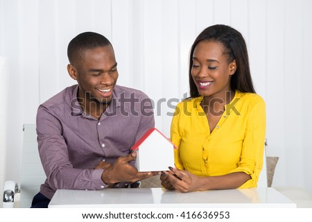 Young Happy African Couple Holding A House Model At Home #416636953