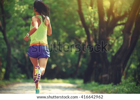 young fitness woman runner running in forest #416642962