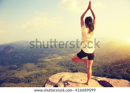 young fitness woman practice yoga at mountain peak cliff #416689099