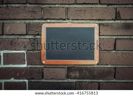 Empty blackboard on a brick wall with copy space. #416755813