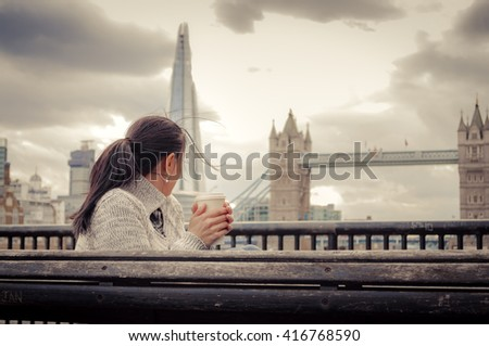 Woman having a cup of coffee in front of the Tower Bridge, in London, England, UK #416768590