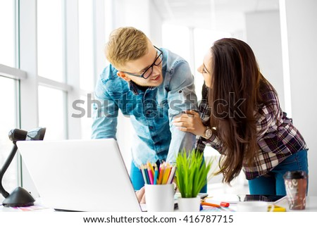 Two young creative designer colleagues using tablet at office #416787715