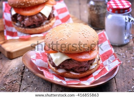 Homemade beef burger with cheese, tomato and pickled onions on a wooden background. #416855863