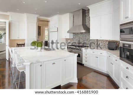 Kitchen Interior with Island, Sink, Cabinets, Oven, Range, and Hardwood Floors in New Luxury Home #416881900