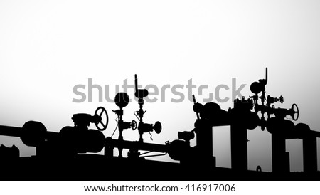 Sunset and silhouette of wellhead manifold controls in the oilfield - black and white #416917006