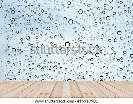 Wood table top on rain drops on clear window - can be used for display or montage your products #416919901