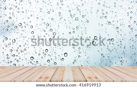 Wood table top on rain drops on clear window - can be used for display or montage your products #416919913