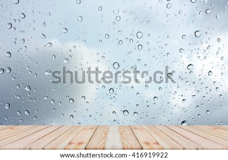 Wood table top on rain drops on clear window - can be used for display or montage your products #416919922