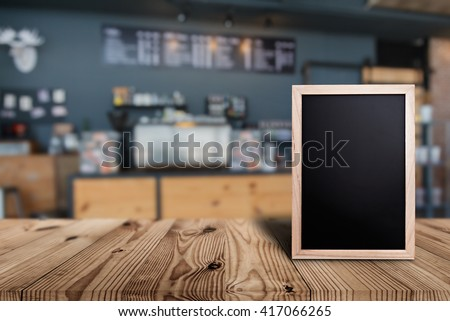 Blank menu board on wooden top table with blurred of coffee shop background Royalty-Free Stock Photo #417066265