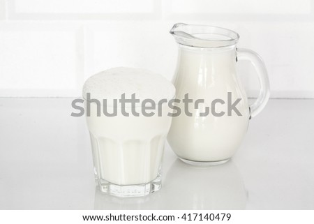 Glass of butttermilk on white table #417140479