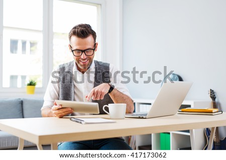 Happy man working from home using digital tablet and laptop #417173062