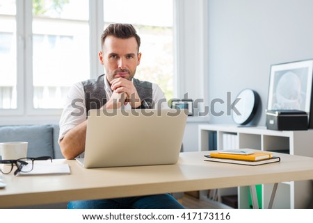Young designer at home office working on laptop looking at camera #417173116